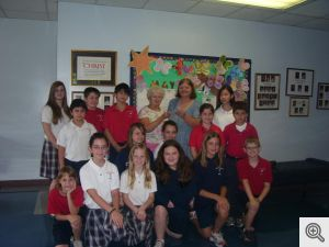 Sheila Harrison, president of Ladies of Sacred Heart, presents a check for $1,200 to Jan Cash, principal at Our Lady of Fatima Catholic School in Benton, AR. The money will be used to update the language arts text books for grades K thru 8. Seventh grade and Fourth grade students in the picture represent the children who will benefit from this donation.
